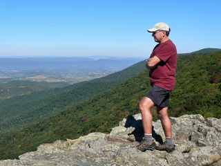 Rich on ledge, mountains and valley in background