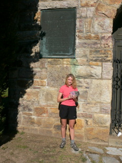 Zhanna holding letterbox, standing by plaque on tower