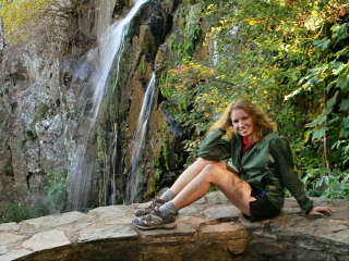 Zhanna on stone wall, colorful leaves, waterfall