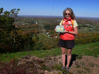 Zhanna displays the cache against a colorful panoramic backdrop.